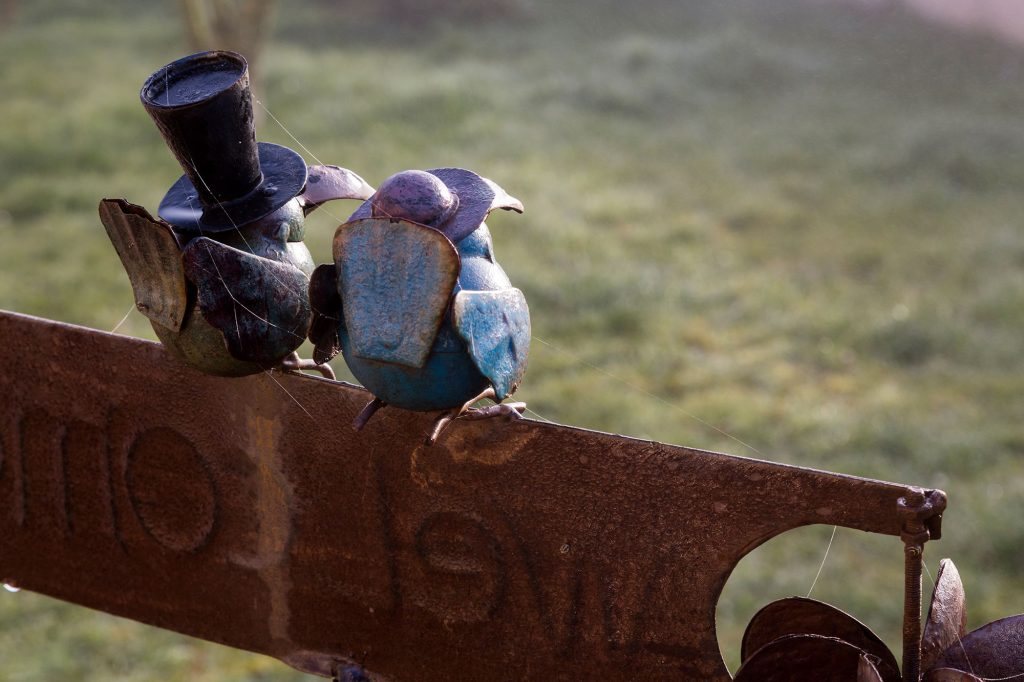 """Sculpture de deux oiseaux perchés sur une pancarte """"Welcome"""" munie d'un anémomètre"""
